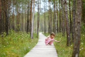 Cute little girl walking in the woods at summer