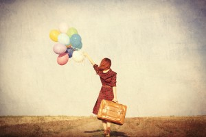 Beautiful girl in plaid dress with multicolored balloons and bag on countryside