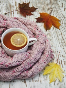 Autumn time: cup of hot tea with lemon and scarf