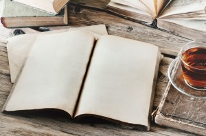 open book with blank pages on wooden table with a cup of tea closeup. Copy space. Free space for test. Top view